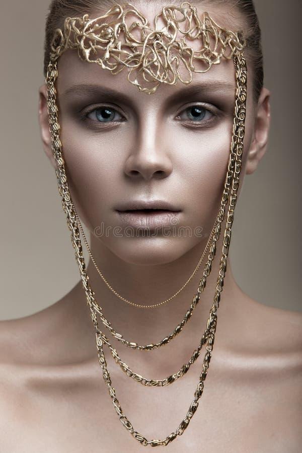 Menina bonita com uma pele de bronze, uma composição pálida e uns acessórios incomuns Imagem da beleza da arte Face da beleza foto de stock royalty free