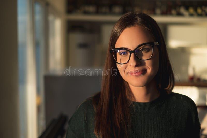 Menina bonita com vidros que sorri e que está pela janela imagem de stock royalty free