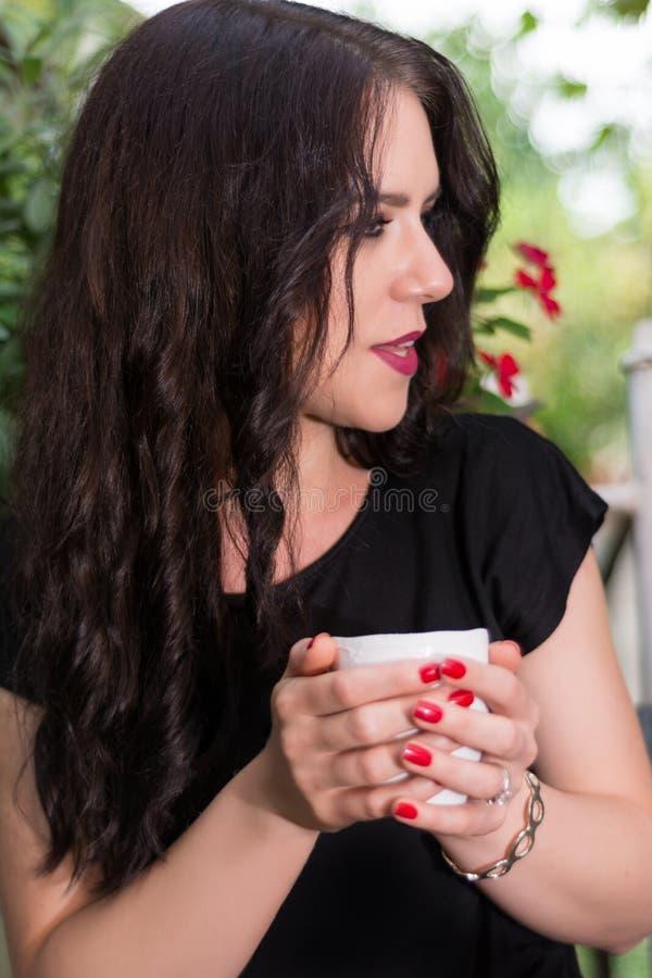 Menina bonita com a xícara de café no parque do jardim que fala e que relaxa imagem de stock royalty free