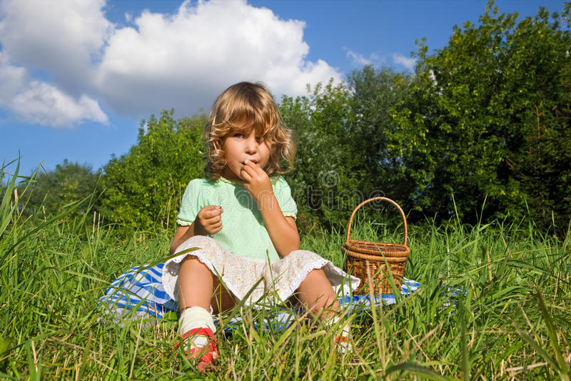 A menina bonita come cerejas doces no jardim imagem de stock royalty free