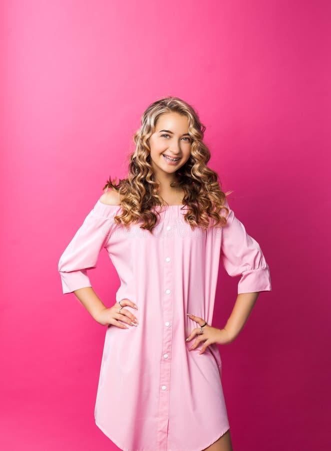 Menina bonita consideravelmente à moda que veste o levantamento cor-de-rosa do vestido foto de stock