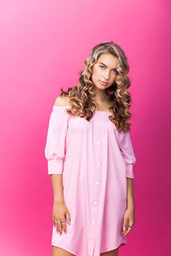 Menina bonita consideravelmente à moda que veste o levantamento cor-de-rosa do vestido imagens de stock