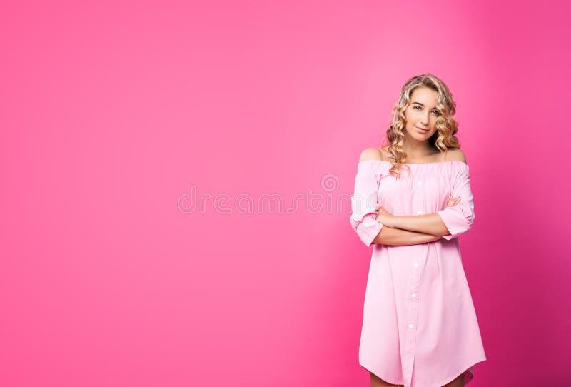 Menina bonita consideravelmente à moda que veste o levantamento cor-de-rosa do vestido fotografia de stock royalty free