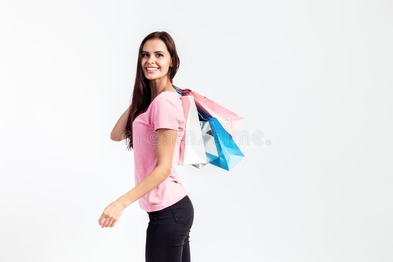 A menina bonita contente vestida no t-shirt e em calças de brim cor-de-rosa está guardando sacos de compras no fundo branco no es foto de stock royalty free