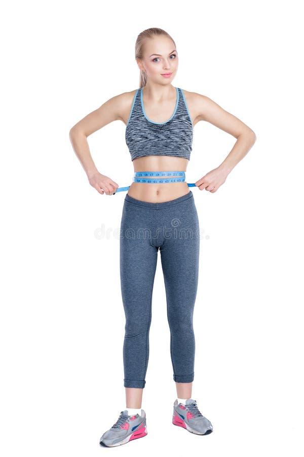 A menina bonita da aptidão no sportswear mede a cintura com a fita de medição no fundo cinzento imagens de stock