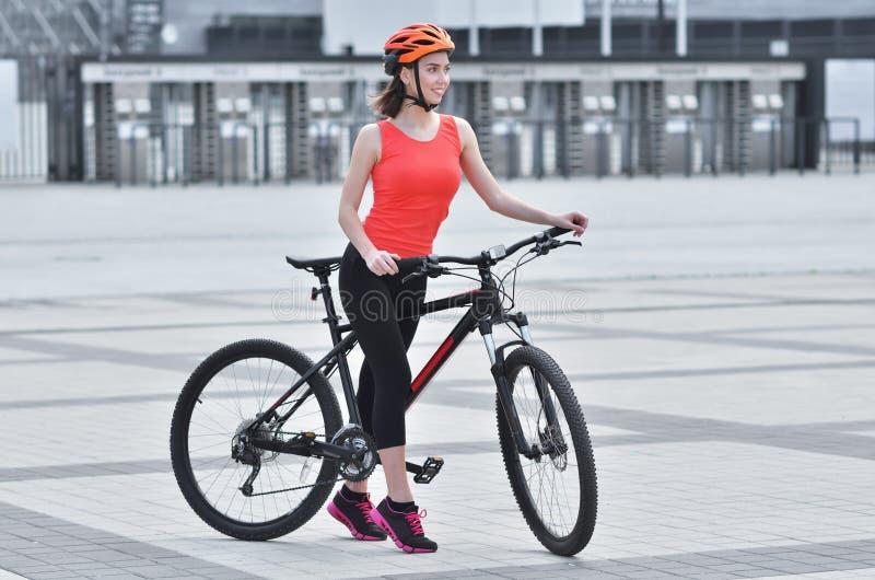 A menina bonita da aptidão vestida no equipamento com bicicleta do esporte está andando foto de stock