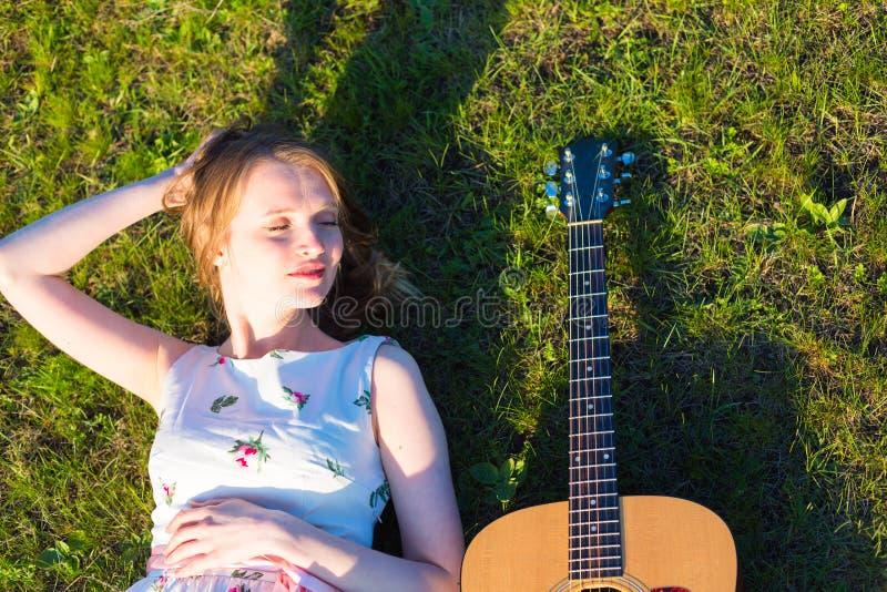 Menina bonita da hippie com a guitarra que encontra-se na grama fotos de stock royalty free