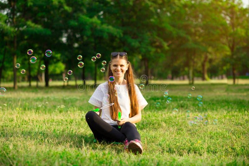 Menina bonita da jovem mulher com jogo de bal?es da bolha no feriado do jardim imagens de stock royalty free