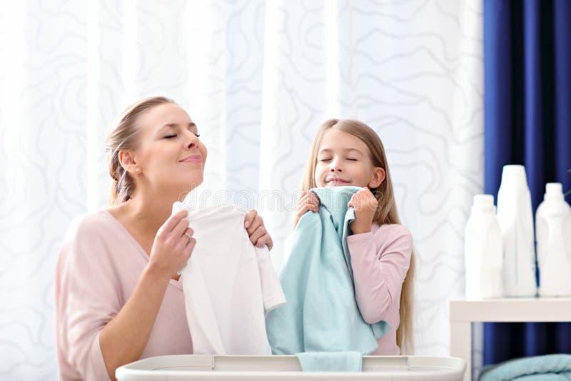 Menina bonita da jovem mulher e da criança que tem o divertimento ao fazer a lavanderia em casa imagens de stock royalty free