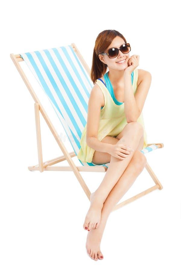 Menina bonita da luz do sol que sorri e que senta-se em uma cadeira de praia fotos de stock