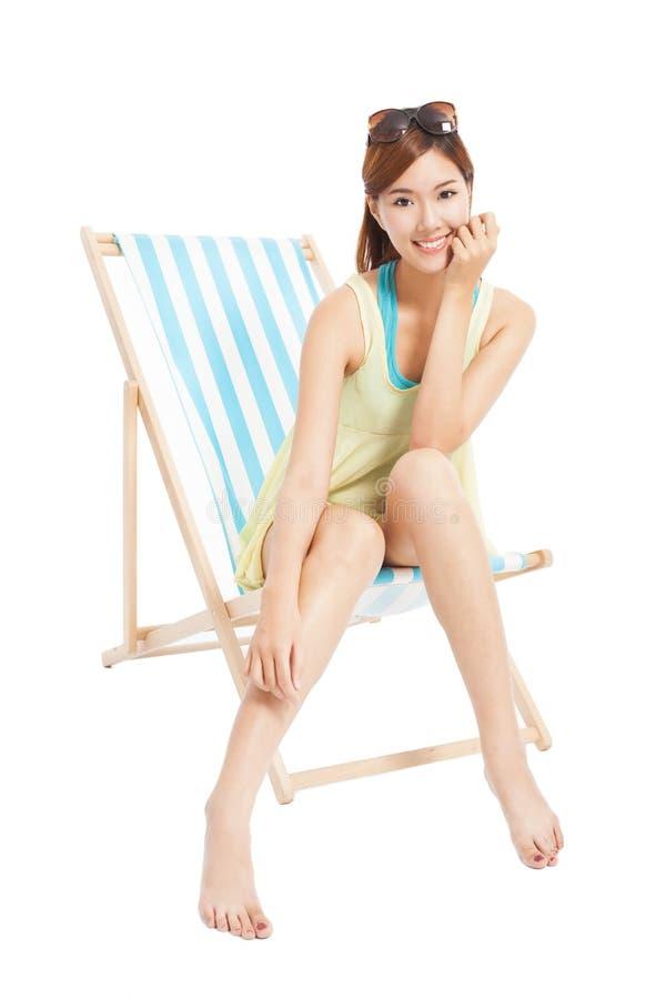 Menina bonita da luz do sol que sorri e que senta-se em uma cadeira de praia fotografia de stock royalty free