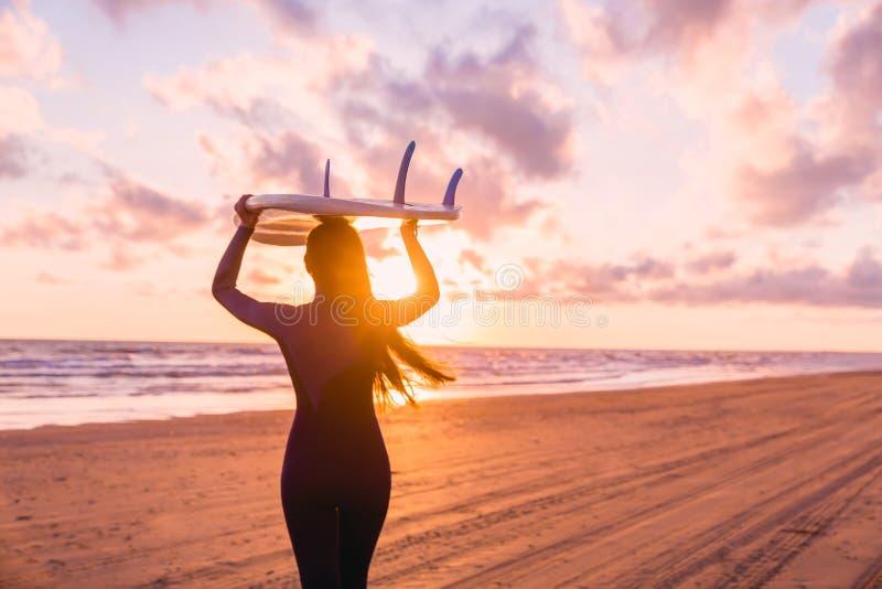 Menina bonita da ressaca da jovem mulher no roupa de mergulho com prancha em uma praia no por do sol ou o nascer do sol e o ocean imagens de stock