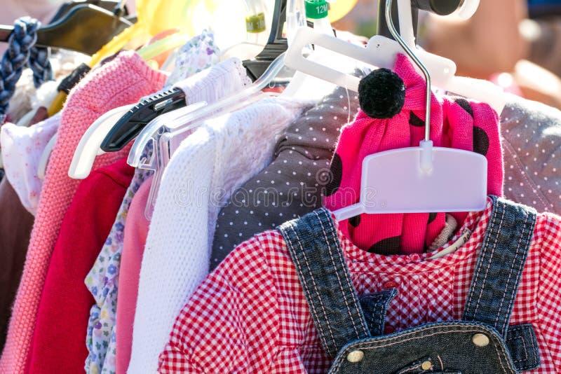 A menina bonita da segunda mão veste-se na venda de garagem à reutilização fotografia de stock