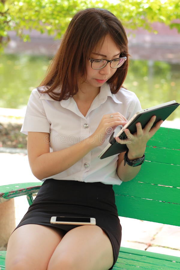 Menina bonita da universidade tailandesa do estudante de mulher que usa sua tabuleta fotos de stock