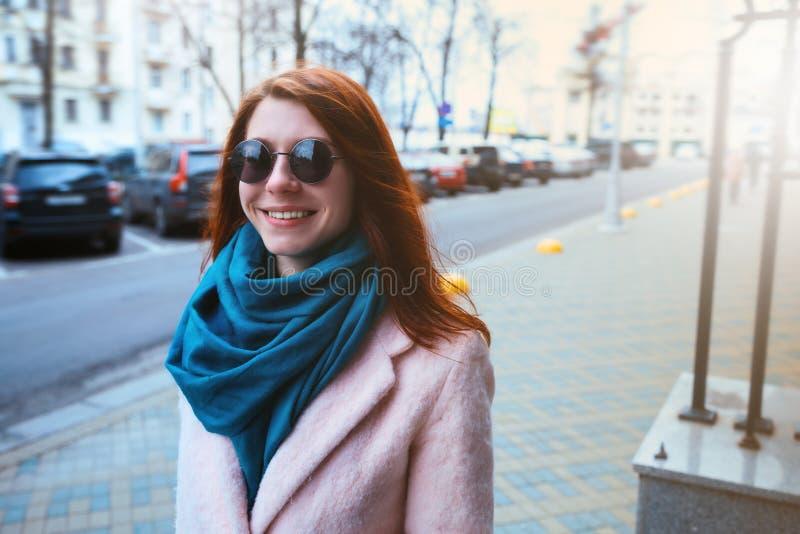 A menina bonita de cabelo vermelha está andando pela rua em um revestimento cor-de-rosa e em um lenço azul, com óculos de sol fotografia de stock