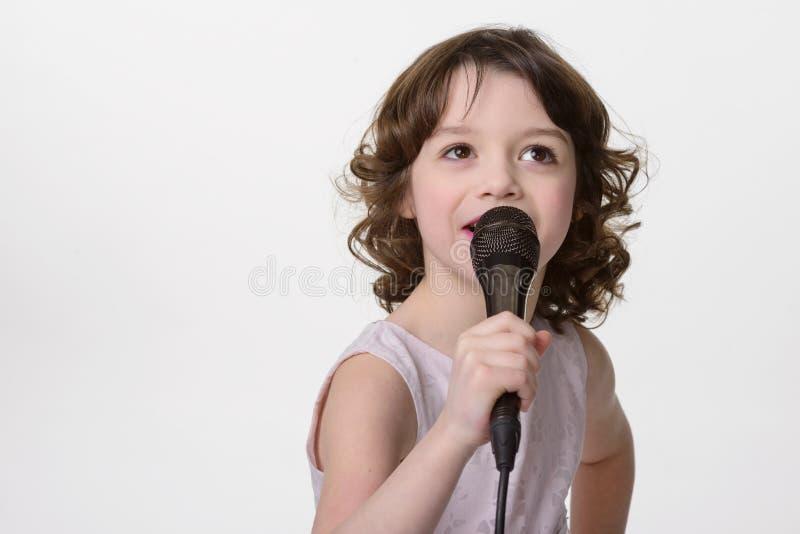 Menina bonita de canto com mic foto de stock royalty free