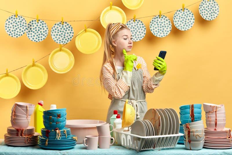 Menina bonita de encantamento nas luvas que guardam o telefone esperto ao fazer pratos fotos de stock
