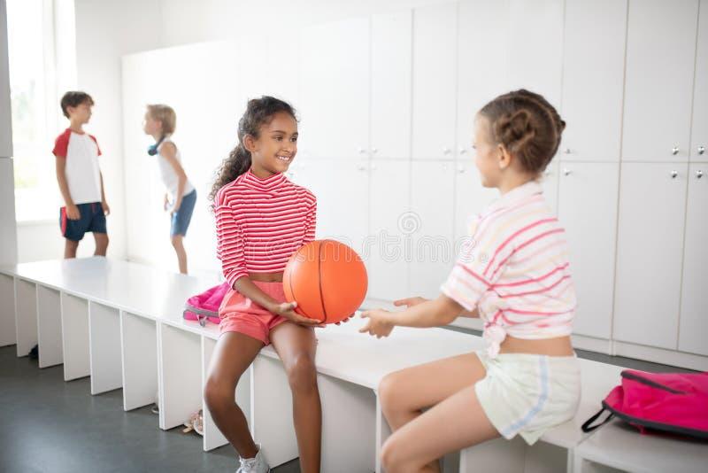 Menina bonita de pele escura dando bola de basquete para um amigo fotos de stock royalty free