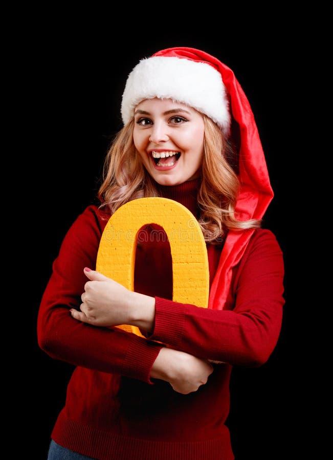 Menina bonita de Santa que guarda um número do amarelo zero em um fundo preto Conceito 2018 do Natal imagens de stock