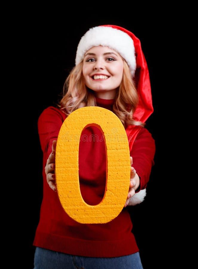 Menina bonita de Santa que guarda um número do amarelo zero em um fundo preto Conceito 2018 do Natal imagem de stock