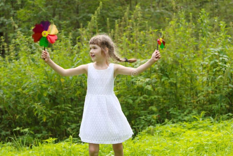 Menina bonita de sorriso com duas rotações dos moinhos de vento imagem de stock