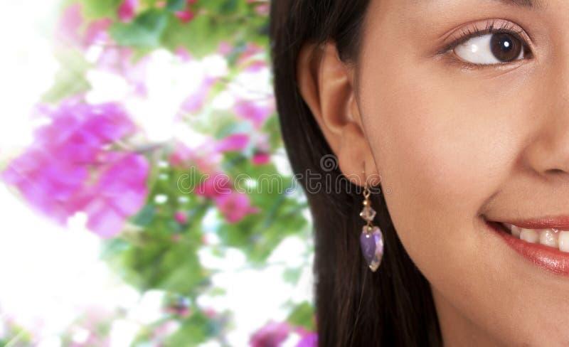Menina bonita de sorriso com fundo das flores fotos de stock