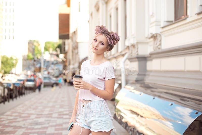 A menina bonita de sorriso com penteado cor-de-rosa do cabelo anda abaixo da rua com uma xícara de café que aprecia um ensolarado foto de stock royalty free