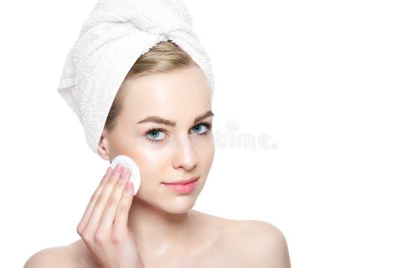 Menina bonita de sorriso com tez perfeita que limpa sua cara usando a almofada de algodão cosmética macia Isolado no fundo branco imagem de stock