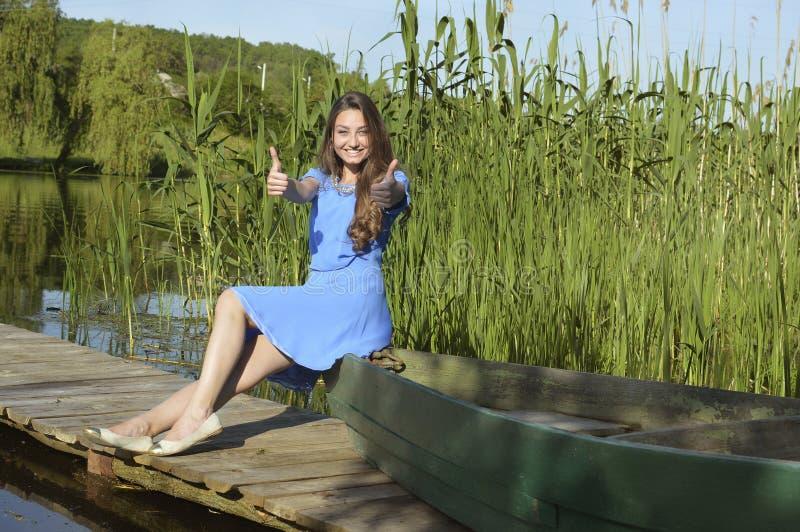 Menina bonita de sorriso dos jovens pelo rio com ela foto de stock royalty free