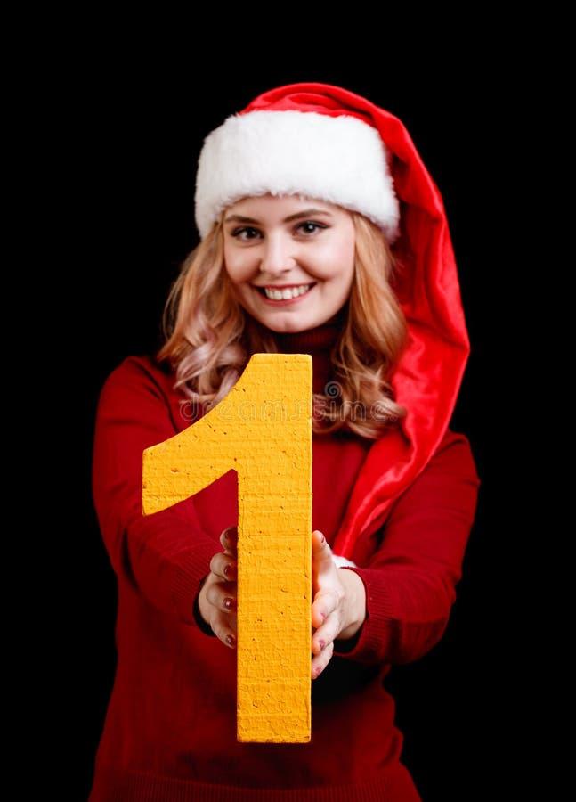 Menina bonita de sorriso em um chapéu do Natal que guarda o número 1 em um fundo preto Conceito 2018 do ano novo imagens de stock royalty free