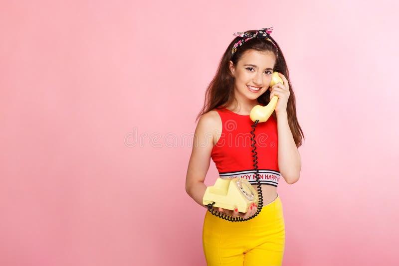 Menina bonita de sorriso, falando no telefone velho da forma em um fundo cor-de-rosa, lugar para o texto Vista horizontal imagens de stock royalty free