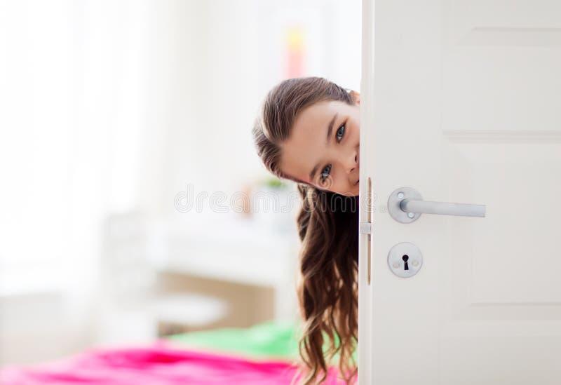 Menina bonita de sorriso feliz atrás da porta em casa imagem de stock