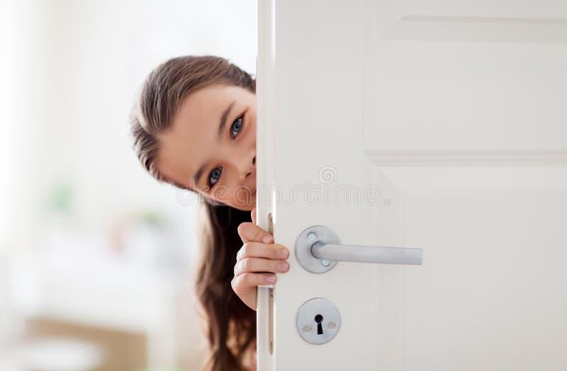 Menina bonita de sorriso feliz atrás da porta em casa foto de stock