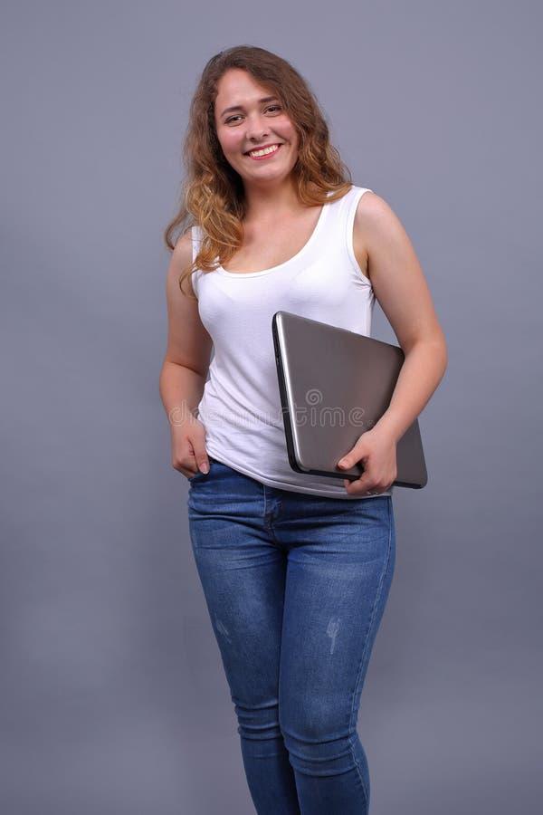 Menina bonita de sorriso no vestuário desportivo que guarda o portátil fotografia de stock