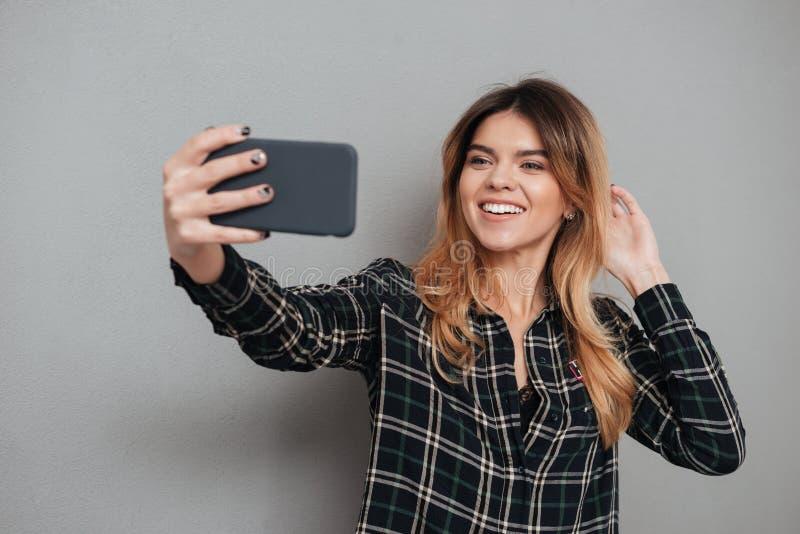 Menina bonita de sorriso que faz um selfie com telefone celular fotos de stock