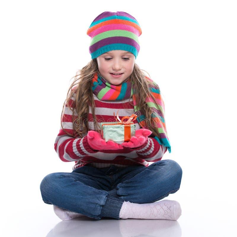 Menina bonita de sorriso que veste o lenço, o chapéu coloful e as luvas feitos malha, mantendo o presente do Natal isolado no fun imagem de stock