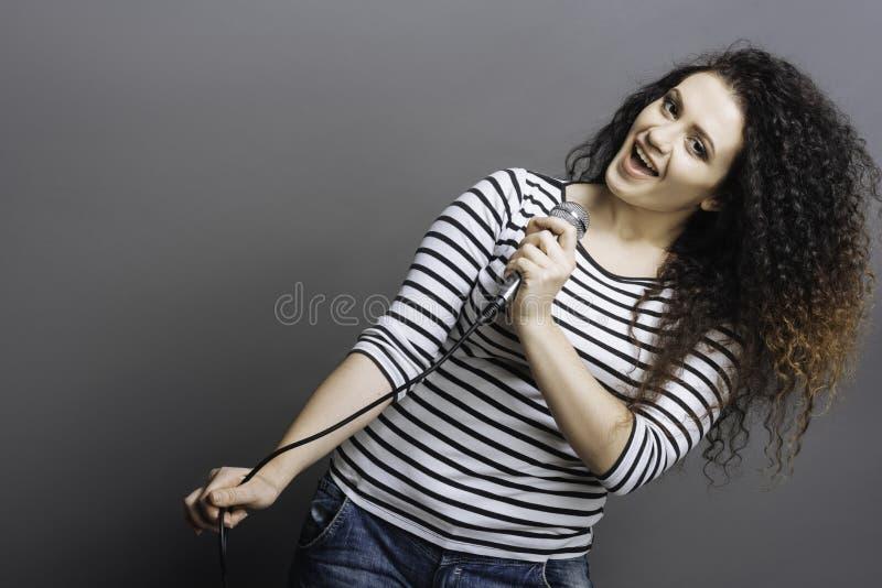 Menina bonita deleitada positiva ao cantar imagem de stock