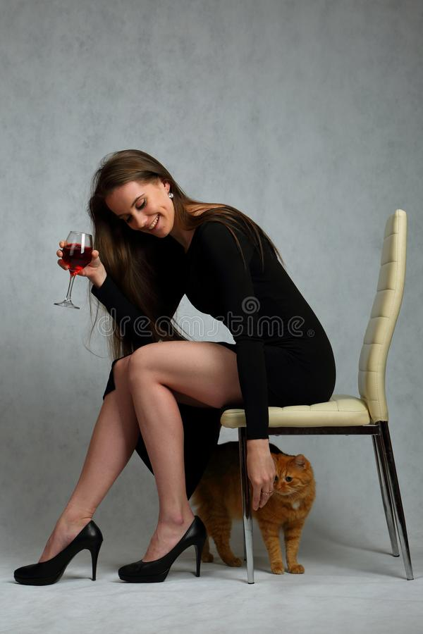 Menina bonita, delgada no vestido preto e gato vermelho fotografia de stock