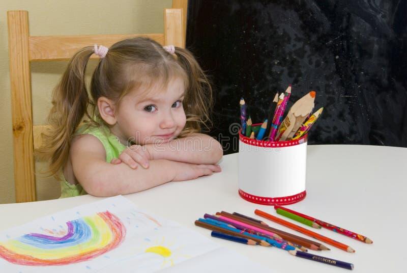 A menina bonita desenhou um arco-íris foto de stock royalty free