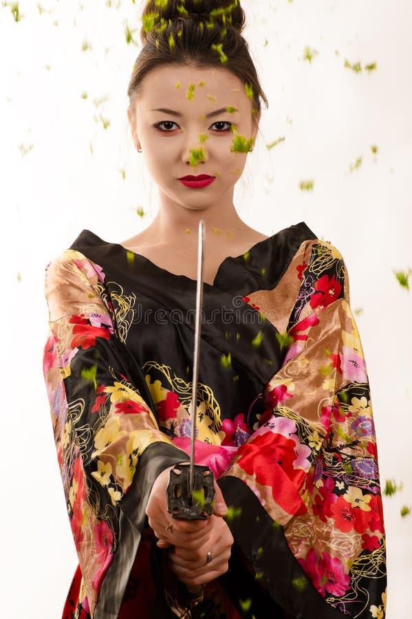 Menina bonita do adolescente com a espada na roupa japonesa imagem de stock