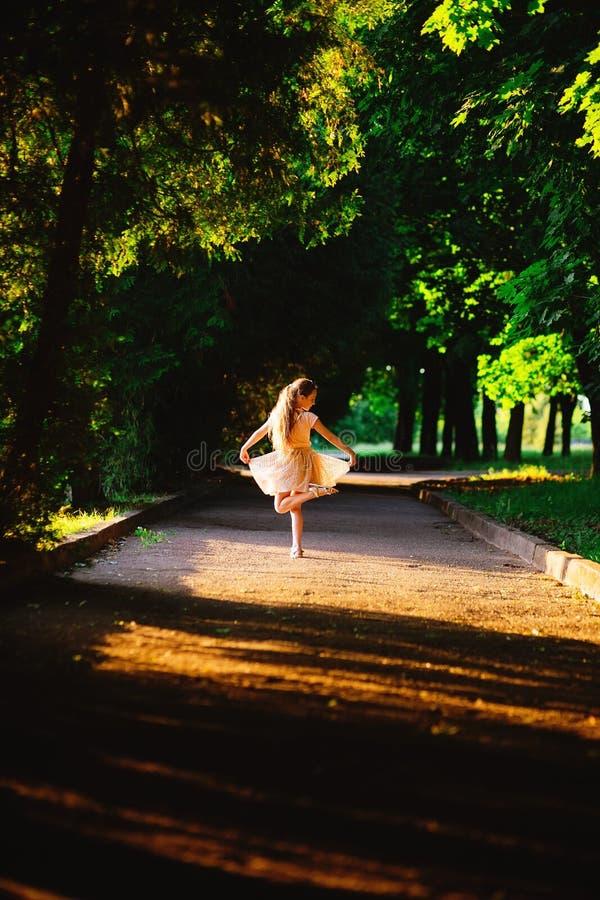 A menina bonita do adolescente está dançando fora no por do sol do verão imagens de stock