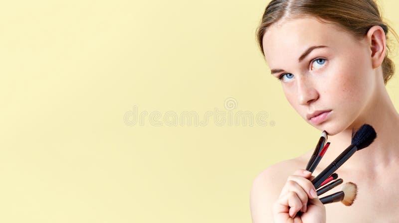 A menina bonita do adolescente do ruivo com olhos azuis e sardas, olhando longe da câmera, guardando diverso compõe escovas fotos de stock royalty free