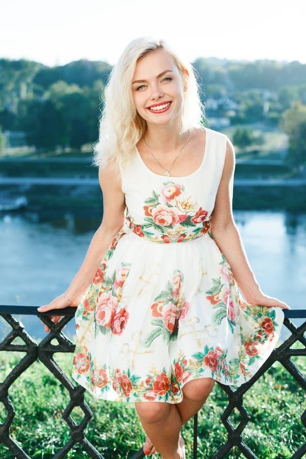 Menina bonita do blondie no vestido no verão perto do rio fotografia de stock