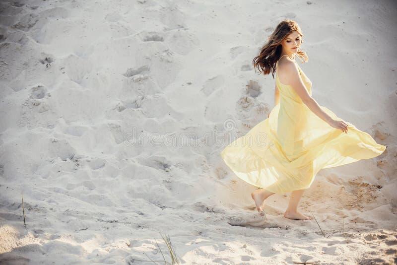 Menina bonita do boho que anda no Sandy Beach na luz do por do sol próximo imagens de stock royalty free
