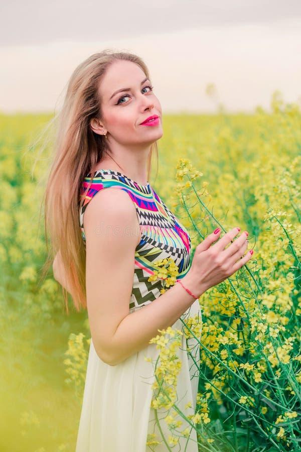 Menina bonita do boho que levanta na câmera no campo do canola imagem de stock royalty free