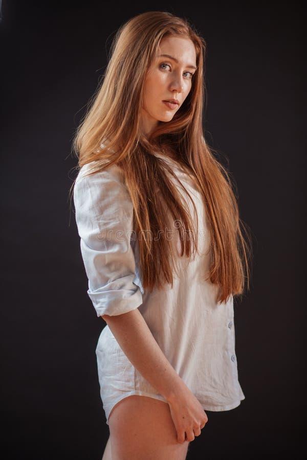 Menina bonita do cabelo do gengibre que levanta olhando a câmera sobre o fundo preto fotos de stock royalty free