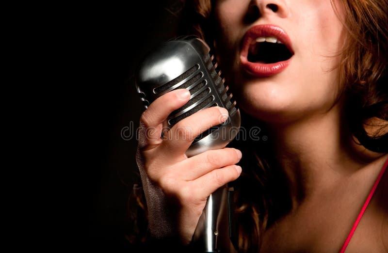 Menina bonita do cantor que canta com microfone foto de stock royalty free