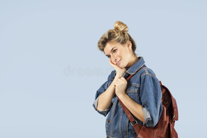 Menina bonita do estudante em um revestimento da sarja de Nimes com uma trouxa em seus ombros no estúdio em um fundo azul O conce imagem de stock royalty free