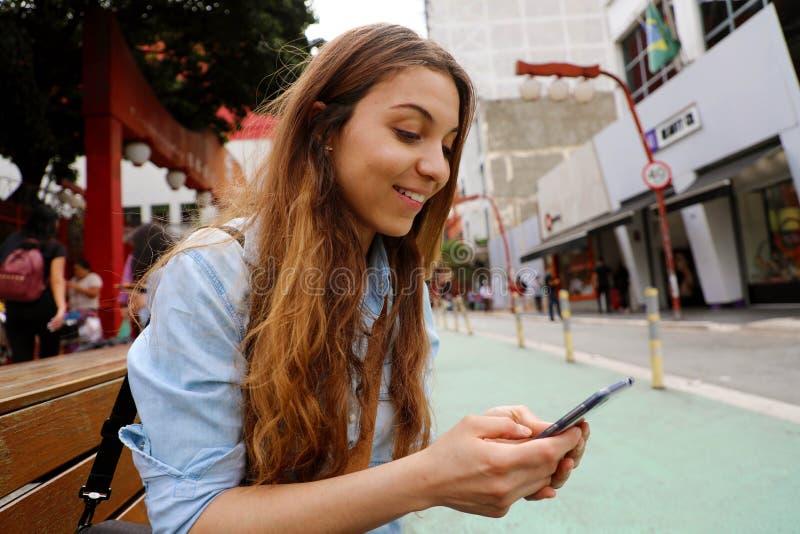 Menina bonita do estudante que senta-se na mensagem do banco da rua com telefone celular no Sao Paulo City, Brasil imagem de stock