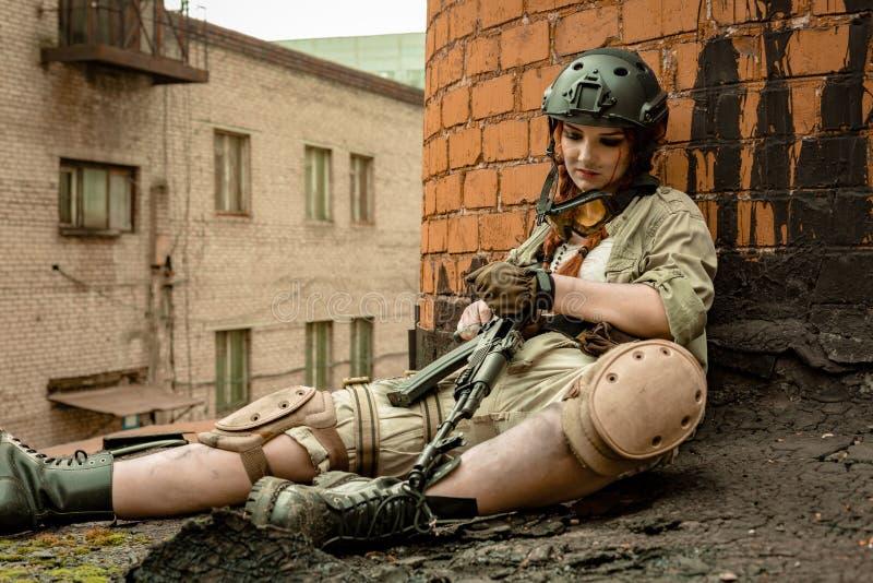 A menina bonita do exército com o rifle na camuflagem veste-se na cena urbana, obtendo o resto fotografia de stock